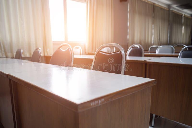 Onderwijsconcept: Lege universiteit of universitair klaslokaal met houten lijsten en stoelen in rij zonder student of leraar in r stock fotografie