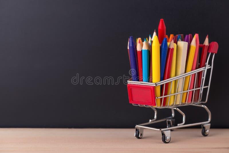 Onderwijsconcept met chroomboodschappenwagentje, pennen, kleurpotloden, colo royalty-vrije stock foto