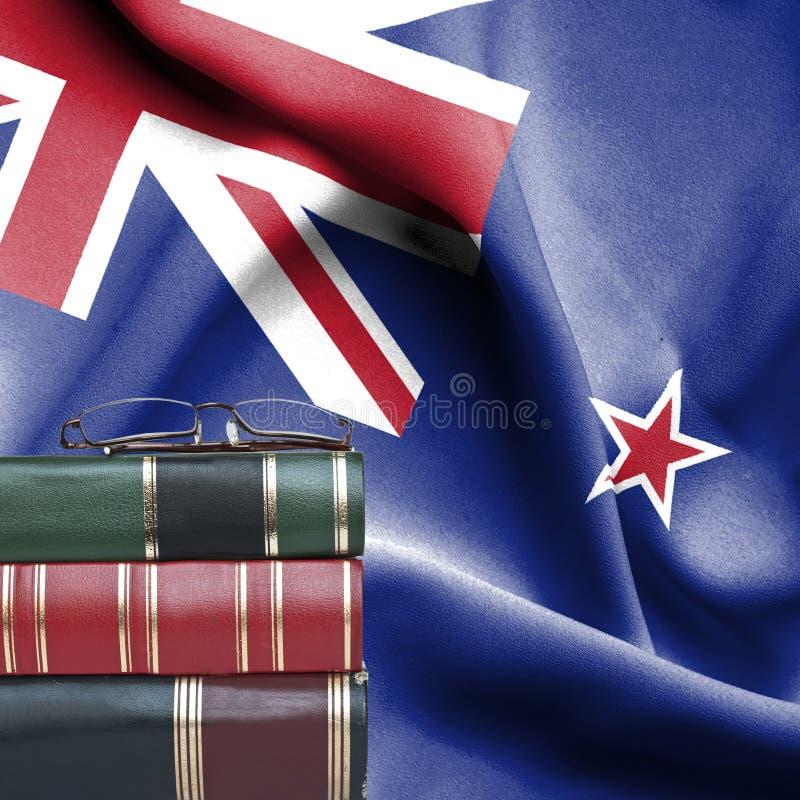 Onderwijsconcept - Stapel boeken en lezingsglazen tegen Nationale vlag van Nieuw Zeeland stock foto
