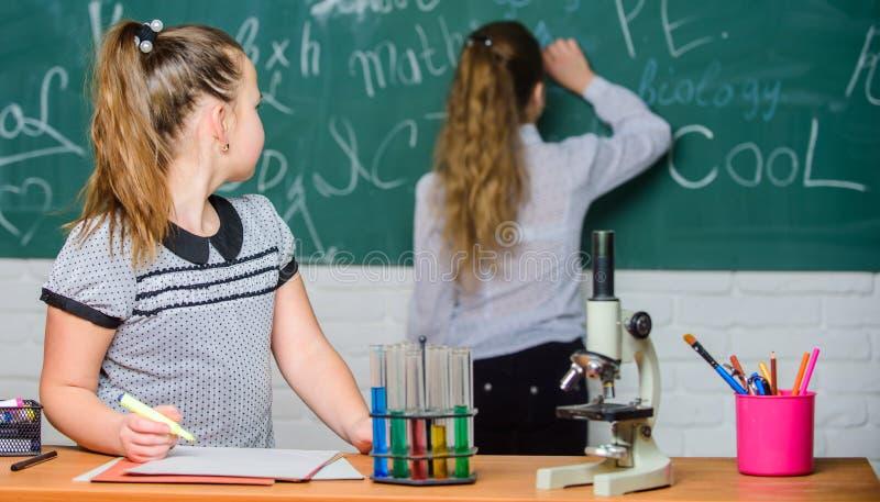 Onderwijsexperimentconcept De meisjesklasgenoten bestuderen chemie Microscoop en reageerbuizen op lijst chemische reacties royalty-vrije stock fotografie