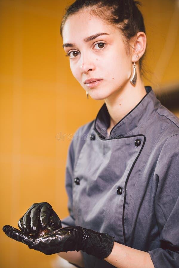 Onderworpen beroep en kokend gebakje jonge Kaukasische vrouw met tatoegering van gebakjechef-kok in keuken van restaurant die ron stock afbeelding