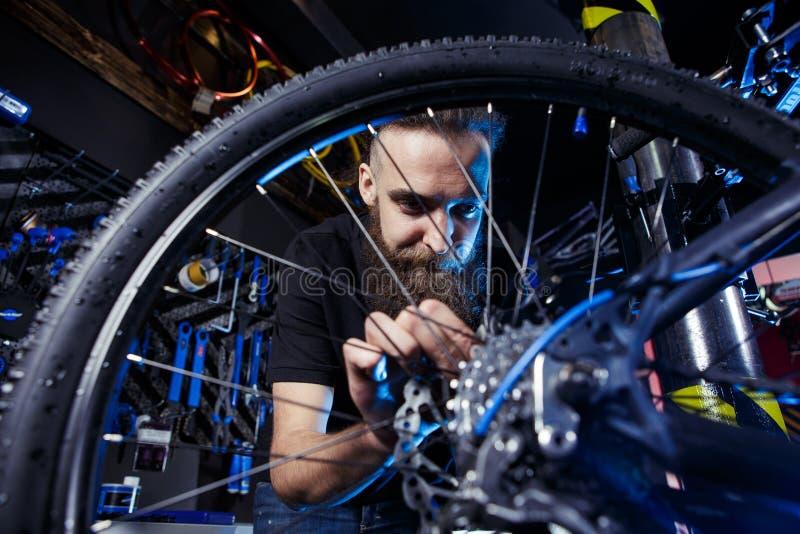 Onderworpen beroep Het jonge modieuze Kaukasische mannetje met een baard op het werk herstelt een fiets Fietswinkel, de dienst en stock fotografie