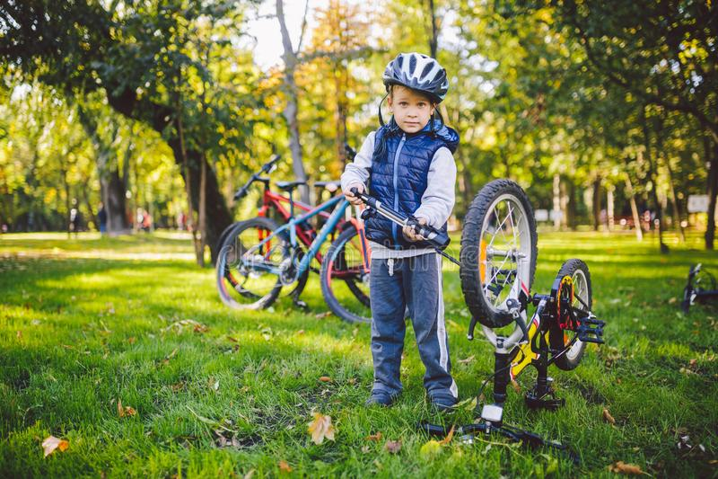 Onderworpen kind en beroep De een weinig blonde Kaukasische jongen gebruikt een fietspomp, pompenlucht in een fiets van het bandw royalty-vrije stock foto