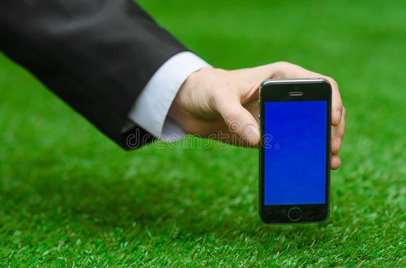Onderworpen mededeling en Zaken: Dien een zwart kostuum in houdend een moderne telefoon met het blauwe scherm op de achtergrond v royalty-vrije stock foto