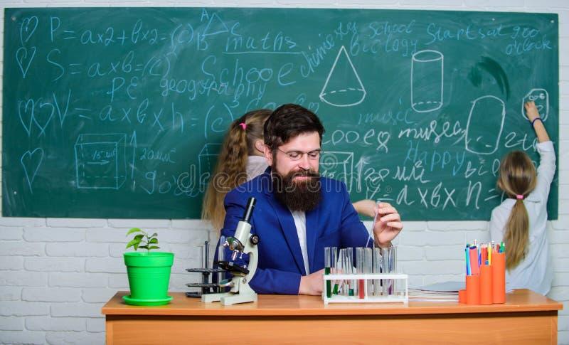 Onderzoek en opleidingsactiviteiten Leraar en basisschoolkinderen in onderzoeklaboratorium Wetenschapsleraar en stock afbeeldingen