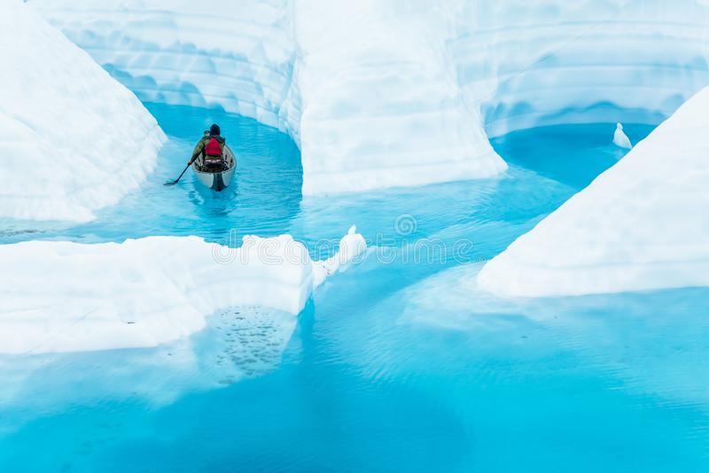 Onderzoekend een smeltende gletsjer door kano die, paddelt een jonge mens in een canion door het verwarmen temperaturen wordt ove stock foto