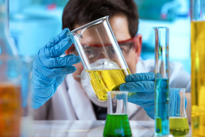Onderzoeker die steekproef in beker vloeistoffen in het onderzoeklaboratorium meten royalty-vrije stock afbeelding