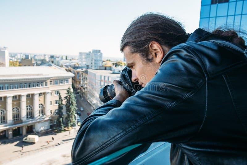 Onderzoeker of privé-detective of verslaggever of paparazzi die foto van balkon van de bouw met professionele camera nemen stock afbeelding