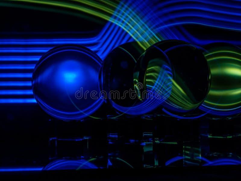 Ondes lumineuses bleues et vertes croisées à l'arrière-plan et se refléter dans le Lenballs photographie stock libre de droits