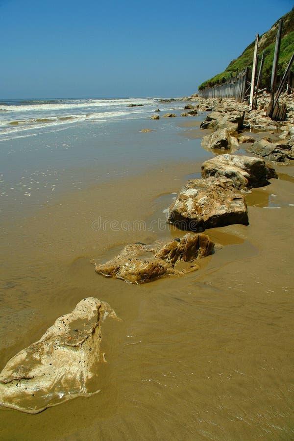 Ondes, plage, frontière de sécurité, roches, et flanc de coteau photo libre de droits