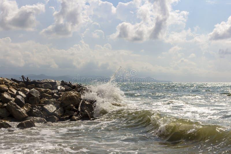 Ondes tombant en panne contre des roches Tempête légère Paysage marin Ciel nuageux photo libre de droits