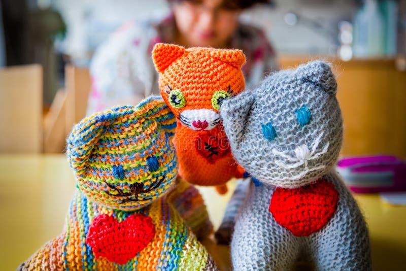 Ondiepe diepte van gebied van drie gebreide gevulde stuk speelgoed katten met rode harten, vrouwenzitting op de achtergrond royalty-vrije stock afbeeldingen