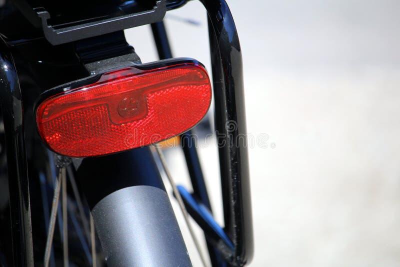 Ondiepe nadruk dichte omhooggaand van de rode achterreflector op een fiets stock foto's