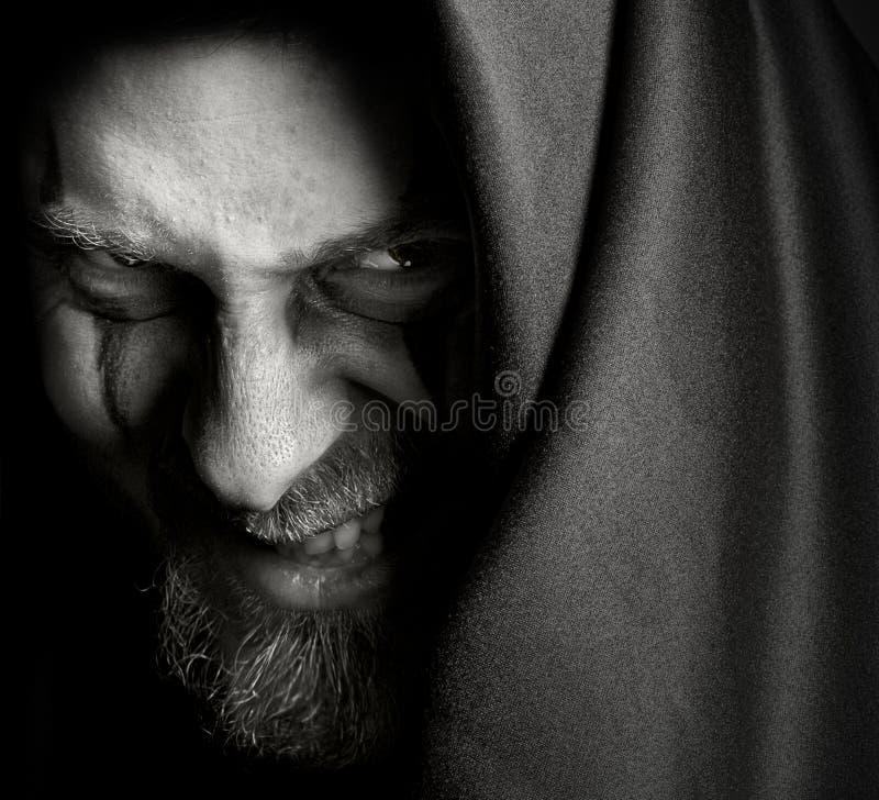 ondskan grinar illavarslande ont för malefic man royaltyfri foto