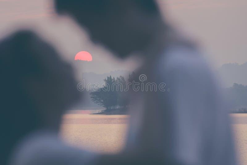 Onduidelijk beeld het houden van de kusscène van het paarsilhouet met zonsondergang stock afbeeldingen