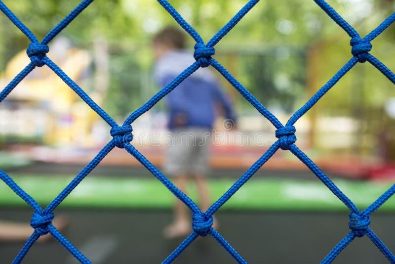 Onduidelijk beeldbeeld die van jong geitje in trampoline op dagtijd springen stock foto