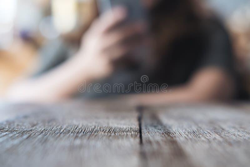 Onduidelijk beeldbeeld van een vrouw die en slimme telefoon houden met behulp van stock afbeeldingen