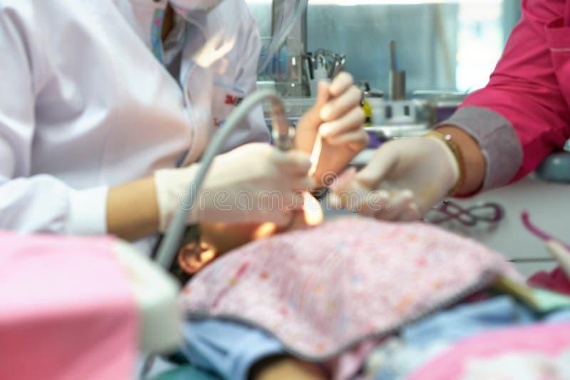 Onduidelijk beeldfoto van van de de ruimtereparatie van het tandartswerk het jonge geitjetanden met medewerker stock foto's