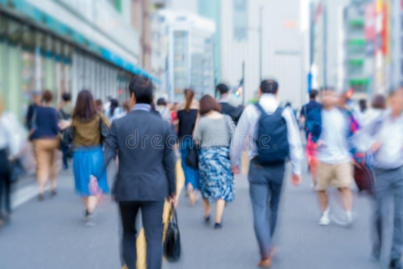 onduidelijk beeldsamenvatting van anonieme mensen die op een straat in stad lopen stock afbeeldingen