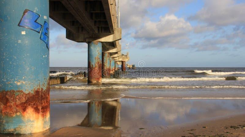 Ondulación en la costa báltica con el puente largo y el triturador de onda de madera foto de archivo