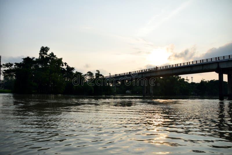 Ondulaciones en el agua, puente a través del bosque en el fondo, con Sun colgando bajo imagenes de archivo