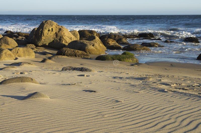 Ondulazioni in sabbia con le rocce e l'oceano immagini stock