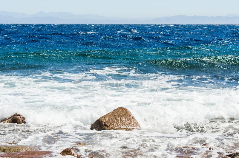 Ondule et éclabousse du ressac et des pierres de mer sur le bord de la mer en Egypte Dahab Sinai du sud photographie stock libre de droits