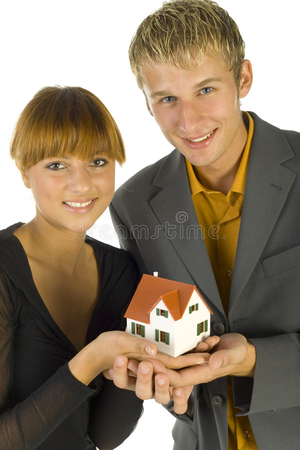 This one!. Young, happy couple holding house miniature. They're looking at camera. Front view, white background stock photography