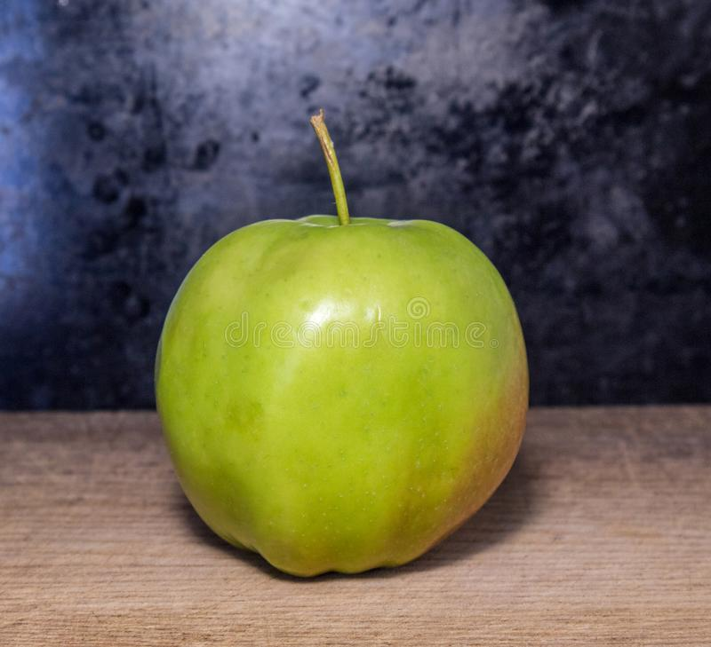One apple on a cutboard royalty free stock image