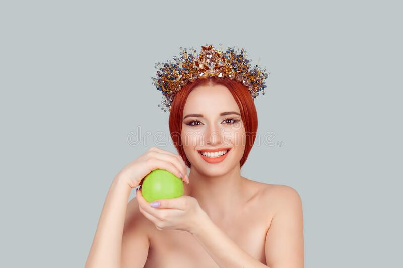 One apple a day keeps doctor away. Beauty queen smiling holding green apple toothy smile pretty woman with crystal crown on head stock image
