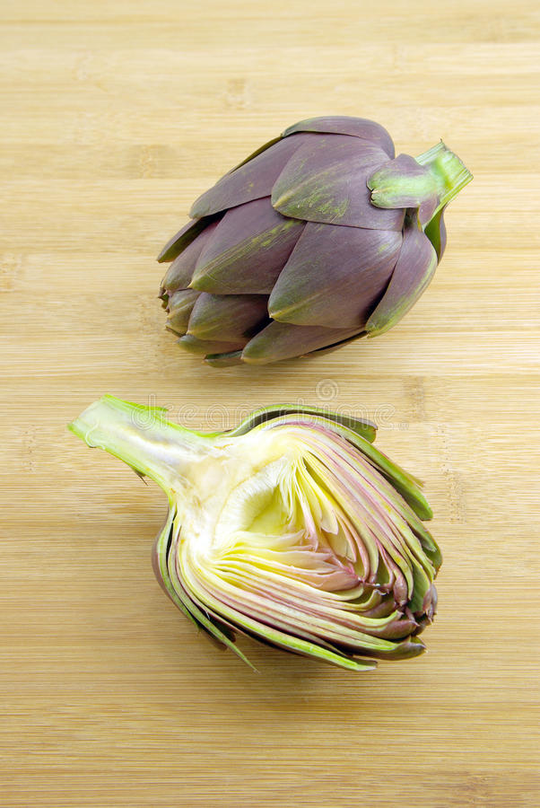 One artichoke and half. One fresh artichoke and half on a wooden chopping board royalty free stock photos