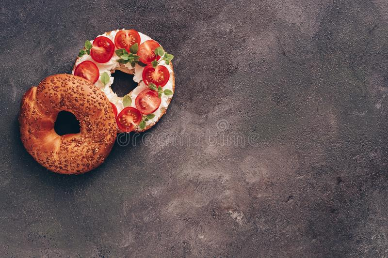 One bagel sandwich with cream cheese, cherry tomatoes,basil on a dark rustic background. Top view, flat lay, copy space royalty free stock photography