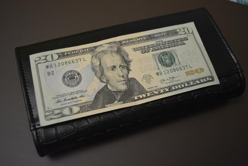 Twenty dollars is on a black wallet made from genuine cowhide leather. One banknote, US currency and dream. Payment for services,. One banknote, US currency and royalty free stock image