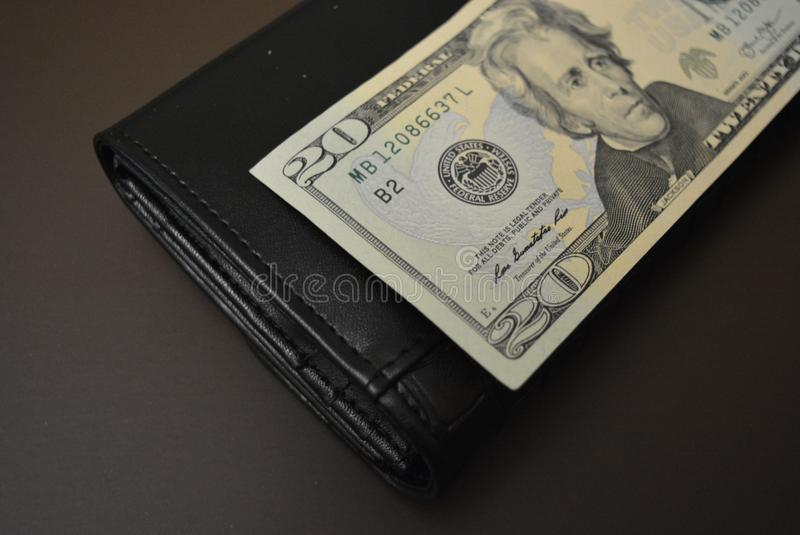 Twenty dollars is on a black wallet made from genuine cowhide leather. One banknote, US currency and dream. Payment for services,. One banknote, US currency and stock photos