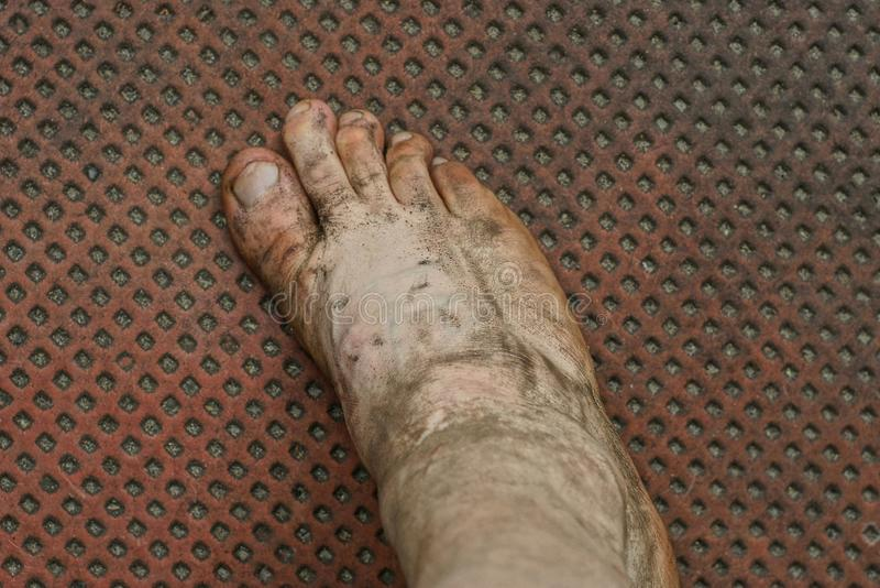 bare foot in gray mud on a brown floor stock photography