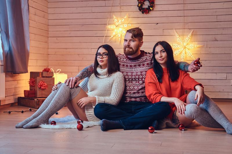 One bearded male and two brunette women Christmas party. stock photo