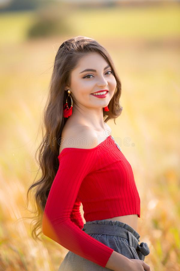 One beautiful female caucasian high school senior girl in red crop top sweater royalty free stock photo
