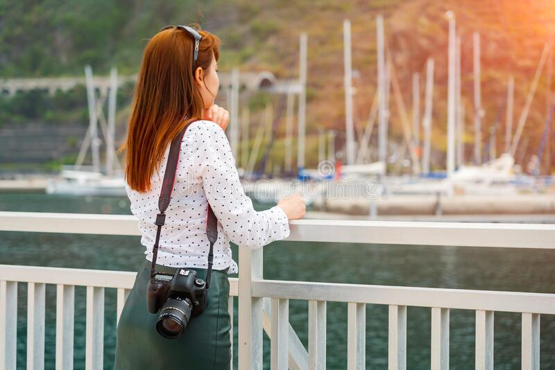 One beautiful readhead girl with camera look at the marina in the sunshine. Woman ready to shoot travel photo on Canary. Islands. Yachts in soft focus on royalty free stock image