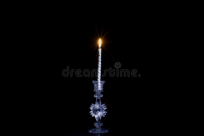 One Beautiful silver candle. Burns in a crystal candlestick on a dark background stock photography