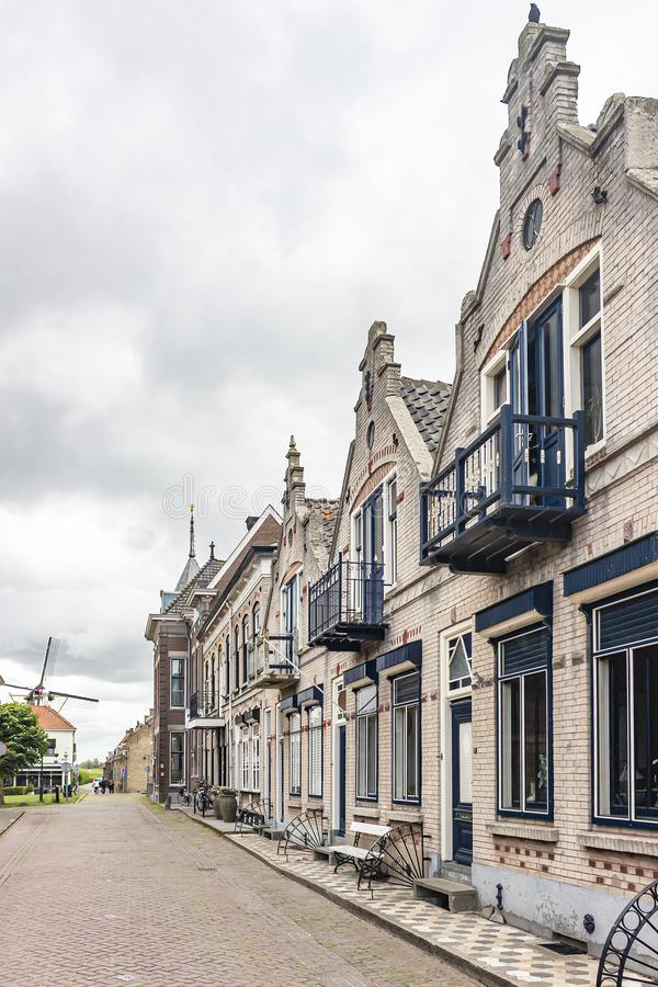 One of the beautiful streets with historic homes and views of the Windmill of Willemstad, Netherlands royalty free stock photo