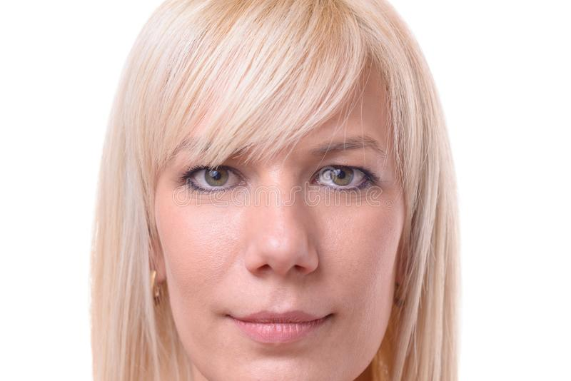 Beautiful young woman with blond hair. One beautiful young woman with blond hair and serious expression and blank stare stock image