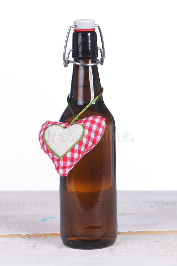 One beer bottle with heart on wooden ground stock image