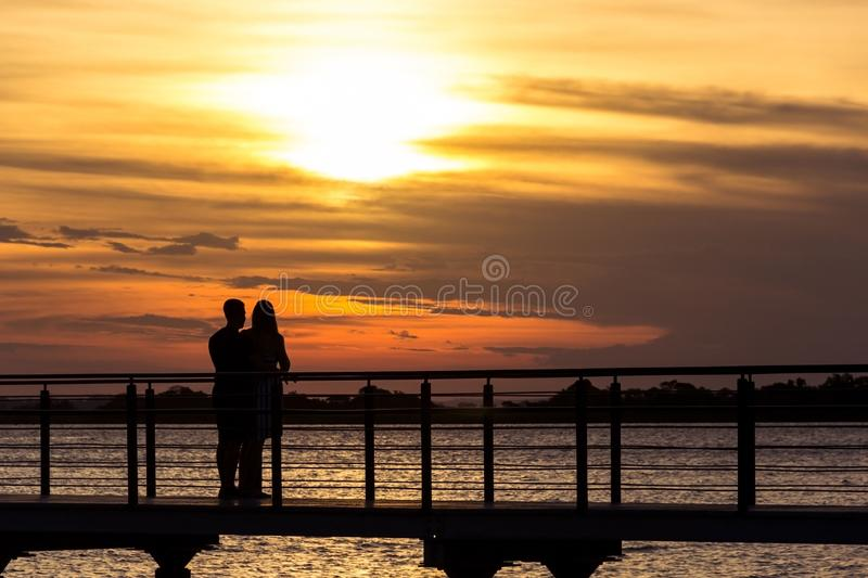 Couple in one of the best sunsets in Brazil. This in one of the best sunsets in brazil. This is the city of Porto Alegre. It is the Guai­ba River and a couple stock photos