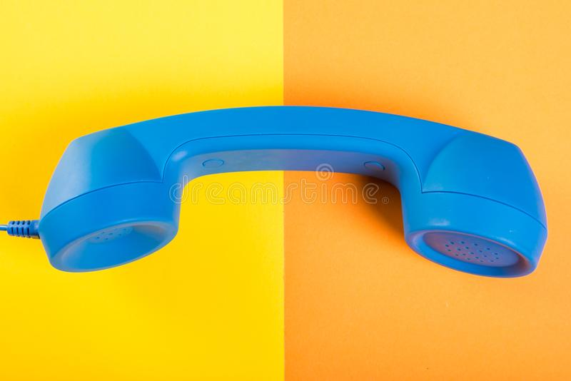 One big blue telephone receiver on yellow and orange background royalty free stock photography