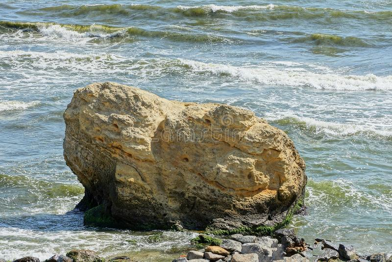 Large brown stone on the beach in water and waves. One big brown stone by the sea in water and waves stock photos