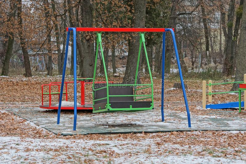 Big colored iron swing on the playground in the winter park stock images