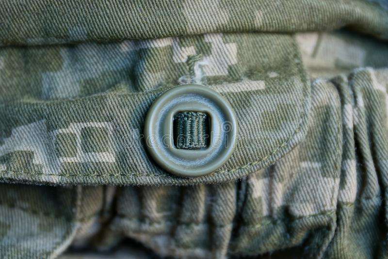 One green button on camouflage army clothes. One big green button on camouflage army clothes stock images