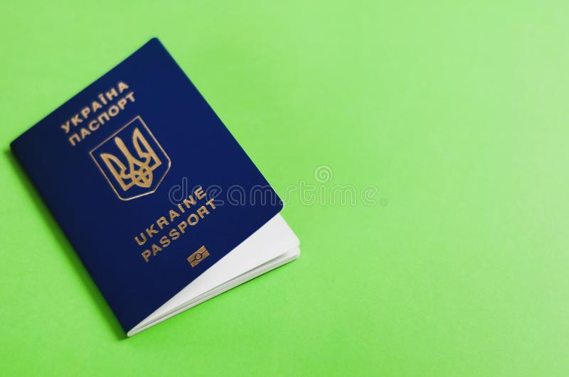 One blue biometric ukrainian foreign passport with coat of arms on green background with copy space royalty free stock image