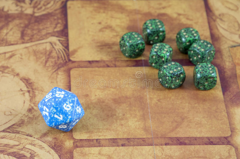 One blue dice with several green dices with number six on them. On the orange background stock photo