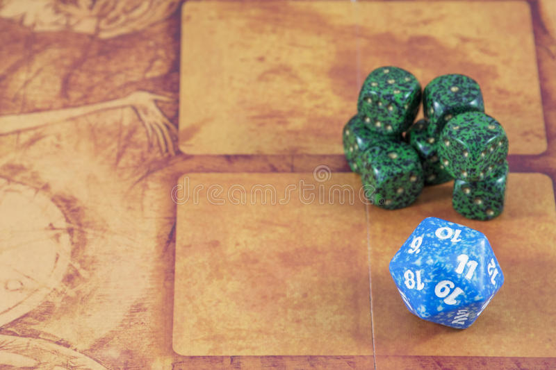 One blue dice with several green dices. On the orange background royalty free stock photography